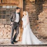 Ines und Peter stehen vor einer alten Mauer für Hochzeitsfotos im Sägewerk in Damme.
